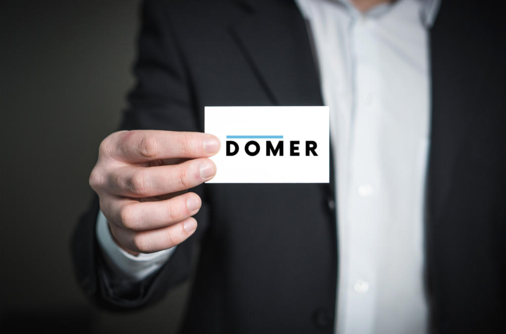 man showing domer business card